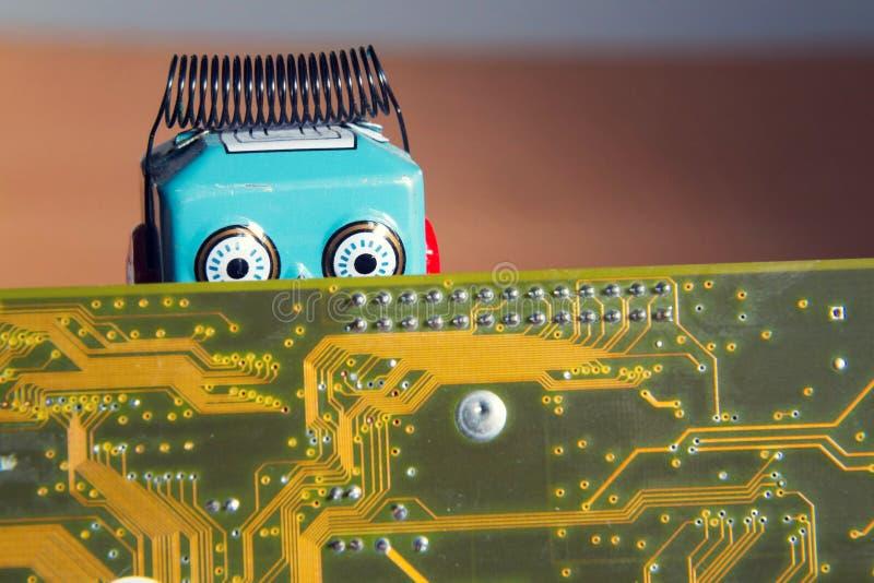 Weinlesezinn-Spielzeugroboter hinter Computerbrett, Konzept der künstlichen Intelligenz lizenzfreie stockfotos