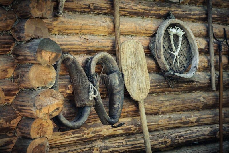 Weinlesezusätze, altes Pferdegeschirr und Haushaltsartikel auf dem Hintergrund einer rauen hölzernen Klotzwand stockfotografie