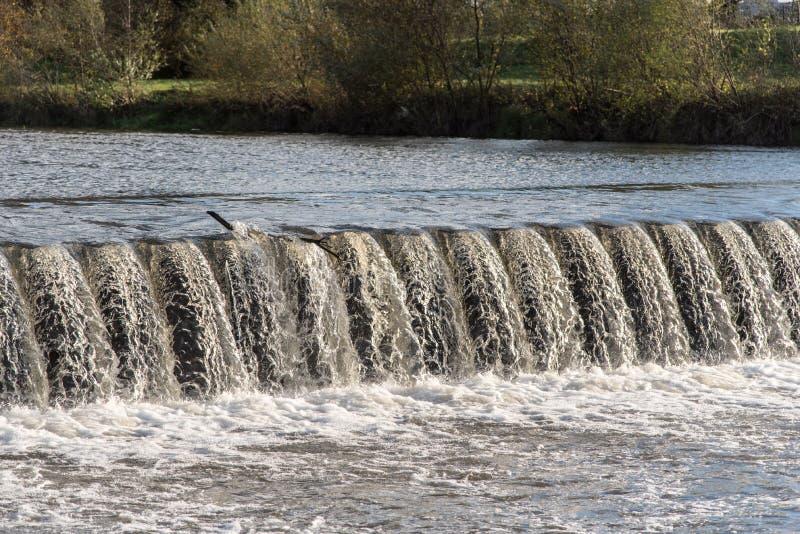 Weir no rio com árvores e grama no fundo imagens de stock royalty free
