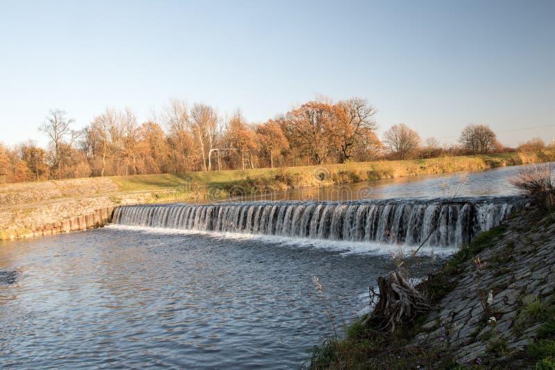 Weir no rio de Olse na cidade de Karvina na república checa com as árvores no fundo fotos de stock royalty free