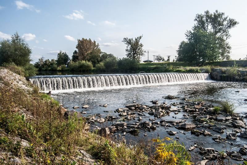 Weir on Olse river in Karvina city in Czech republic. Weir on Olse river with trees around and blue sky with clouds in Karvina city in Czech republic stock images