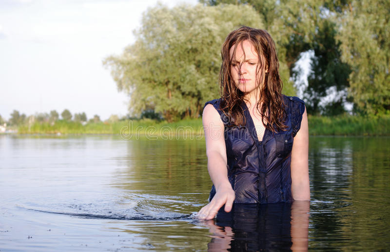 Weird clothed bather woman. Weird clothed bather redhead pensive woman stock photography