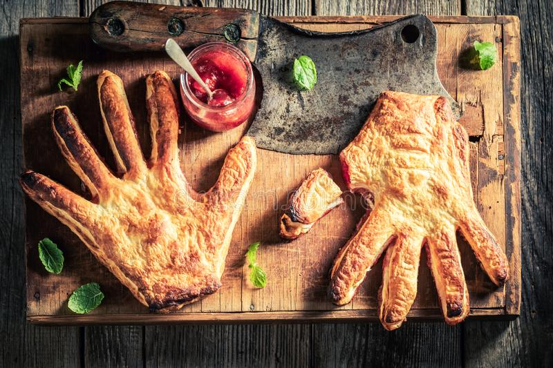 Weird hand cake with a chopper as concept of liking. On wooden table royalty free stock images