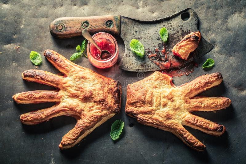 Weird hand cake with a chopper as liking concept. On metal table royalty free stock image