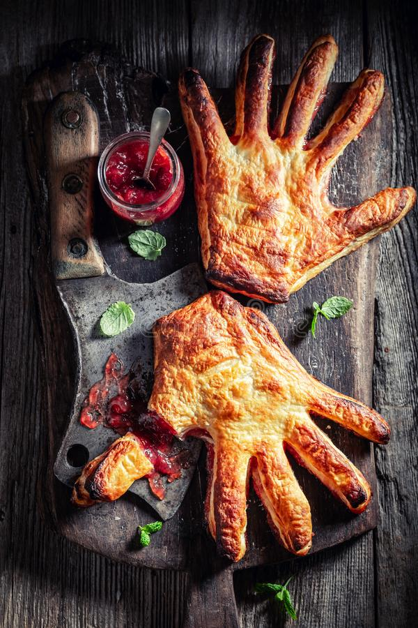 Weird hand cake with strawberry jam as concept of liking. On wooden table stock image