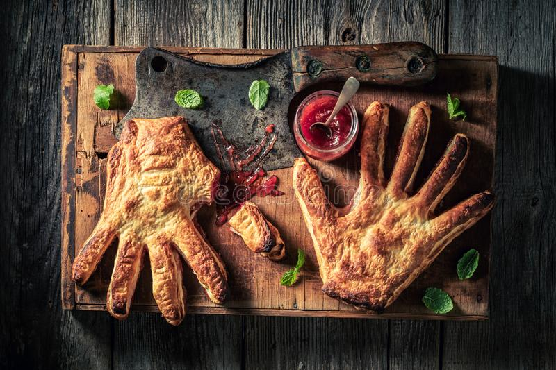 Weird hand cake with strawberry jam as liking concept. On wooden table royalty free stock photography