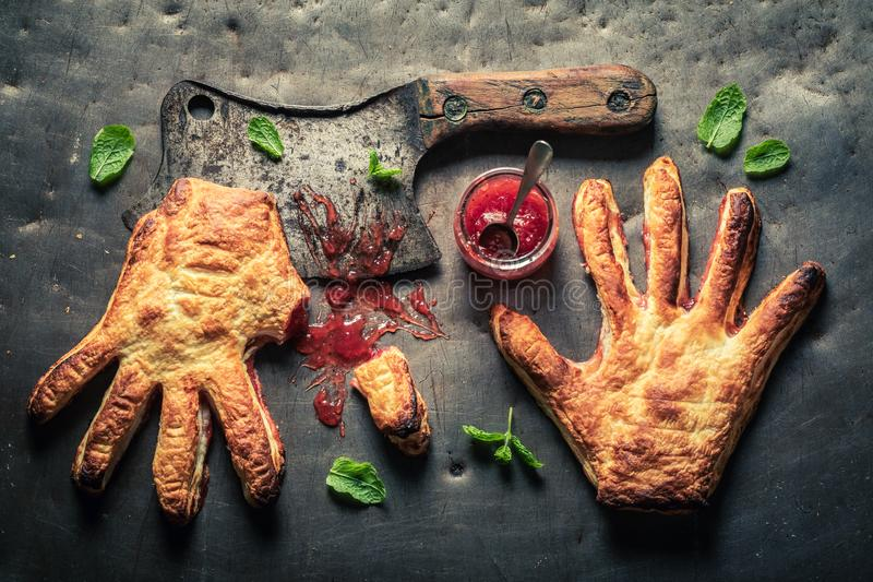 Weird hand cake with thumb cut off as liking concept. On wooden table stock photos