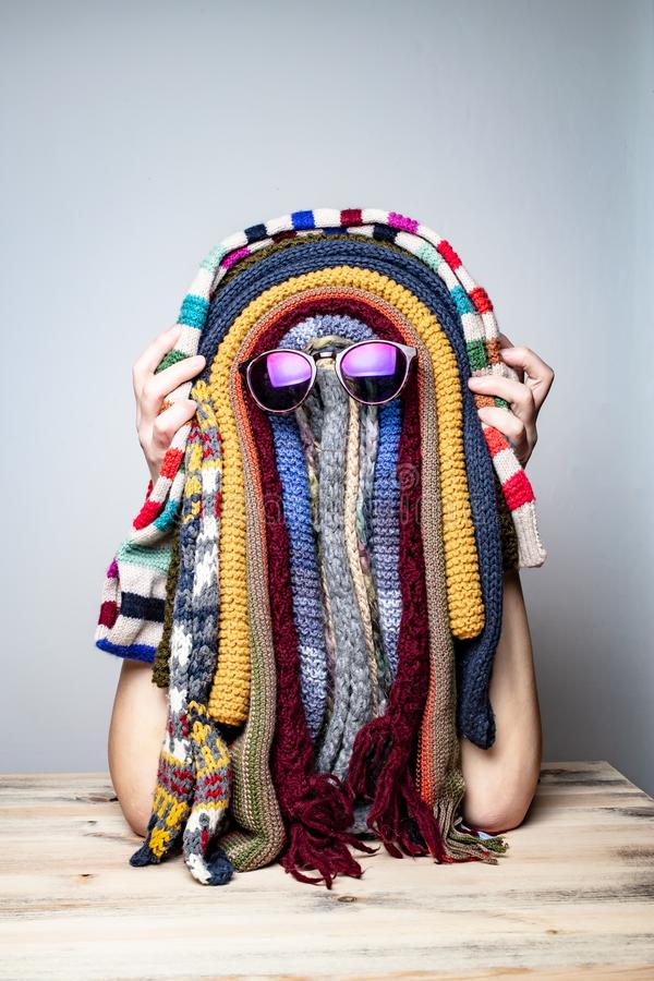 Weird strange girl is fooling around in the winter waiting for summer and jokingly makes a funny mask of colorful scarves in the stock photo