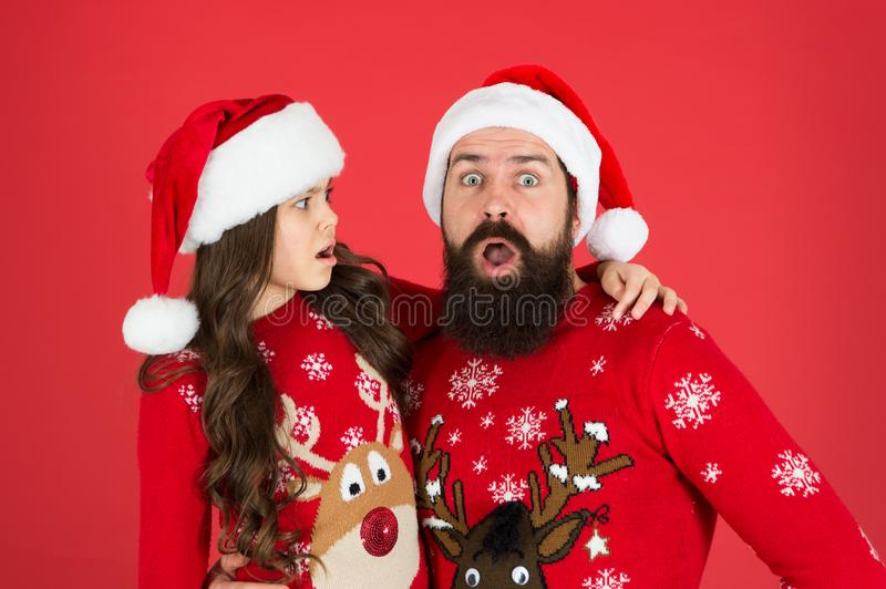 Weird things going on. Father and daughter winter sweaters celebrate new year. Happy family hug. Concentrated faces stock image
