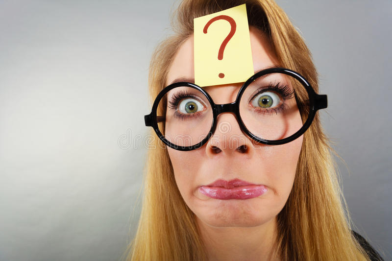 Weirdo nerd woman having question mark on forehead. Crazy wondering face expression concept. Wierdo nerd woman having question mark on forehead and geek royalty free stock image