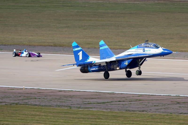 WEISS Mikoyan Gurevich MiG-29UB 1 des perfoming Rennens der russischen Luftwaffe mit Auto der Formel 3 in Zhukovsky während des a stockbilder