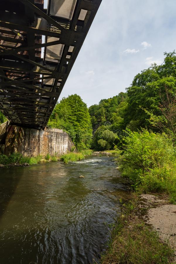 Weisse Elster river with railway bridge above and trees around between Plauen and Elsterberg towns in Germany. During nice summer day with blue sky stock images
