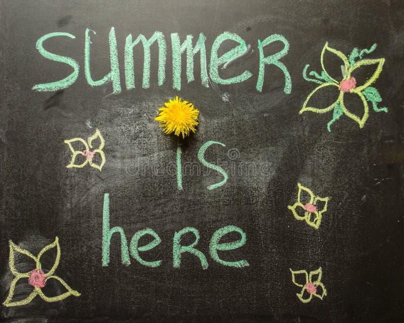 Weissen Sie handgeschriebenen Aufschrift Sommer ist hier auf einer schwarzen Tafel Helles gelbes L?wenzahnteil der Aufschrift stockfotos