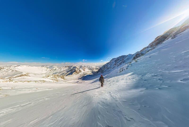 Weitwinkelansicht eines Gebirgswanderers, zum eines Berges des Schnees zu klettern stockfotos