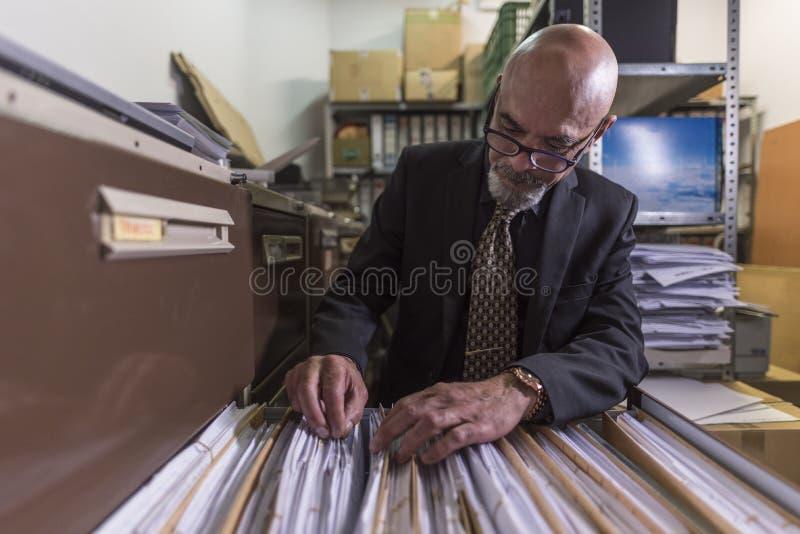 Weitwinkelbild des älteren Mannes Dateien schauend stockfotos