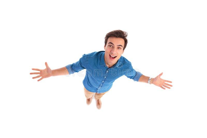 Weitwinkelbild eines aufgeregten jungen zufälligen Mannbegrüßens lizenzfreie stockfotografie