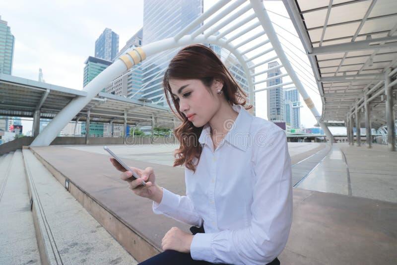 Weitwinkelschuß der attraktiven jungen asiatischen Geschäftsfrau, die intelligentes Mobiltelefon am Gehweg außerhalb des Büros ve lizenzfreies stockfoto