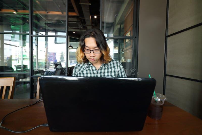 Weitwinkelschuß des jungen asiatischen Mannes, der mit seinem Laptop im Konferenzzimmer des Büros arbeitet lizenzfreies stockbild