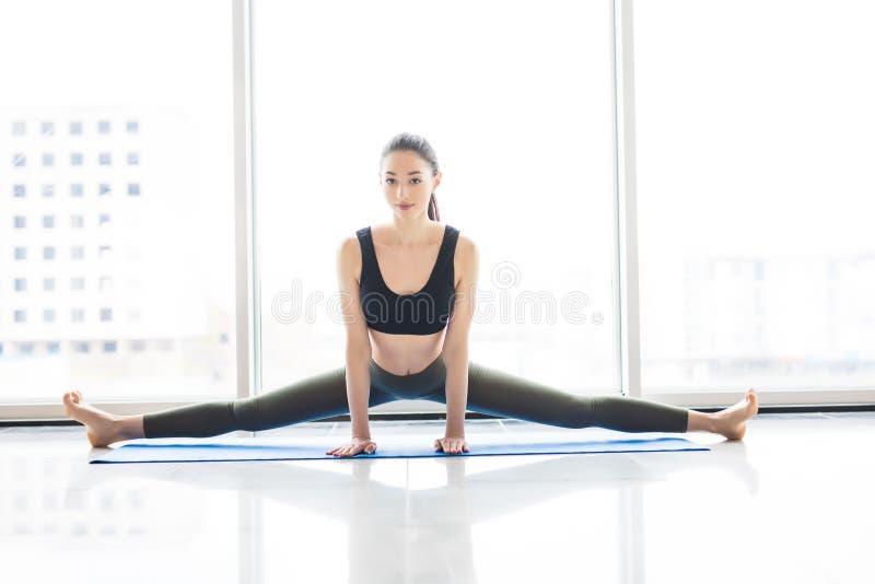 Weitwinkelsitzrumpfbeuge Übendes Yoga der jungen attraktiven Frau, stehende Yogaübung, tragende Sportkleidung nahe Bodenwind stockfotografie