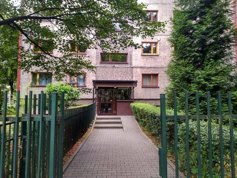 Wejście stary szary budynek przez alei zieleni krzaki wejściowy metal z szklanym drzwi, żelaza ogrodzenie otacza a obraz stock