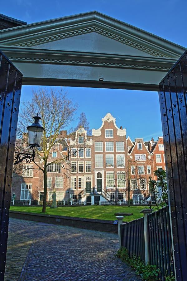 Wejściowa brama wewnętrzny podwórze Begijnhof, jeden starzy hofjes w Amsterdam, z statuą jezus chrystus fotografia stock