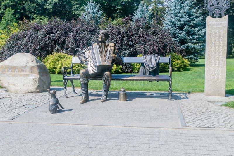 Bench with playing Kaszuby on accordion at park in Wejherowo. Wejherowo, Poland - August 2, 2018: Bench with playing Kaszuby on accordion at park in Wejherowo stock image