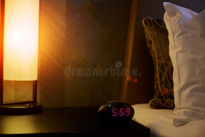 Wekker dichtbij het bed in slaapkamer stock fotografie