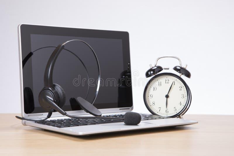 Wekker die zich door laptop met hoofdtelefoon bevinden royalty-vrije stock fotografie