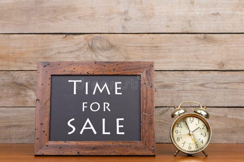 Wekker en bord met tekst 'Tijd voor verkoop stock afbeelding