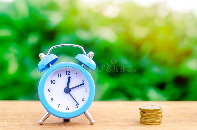 Wekker en geld op groene bokehachtergrond Het concept tijd is geld bedrijfs financiële ideeën besparing financieel royalty-vrije stock afbeelding