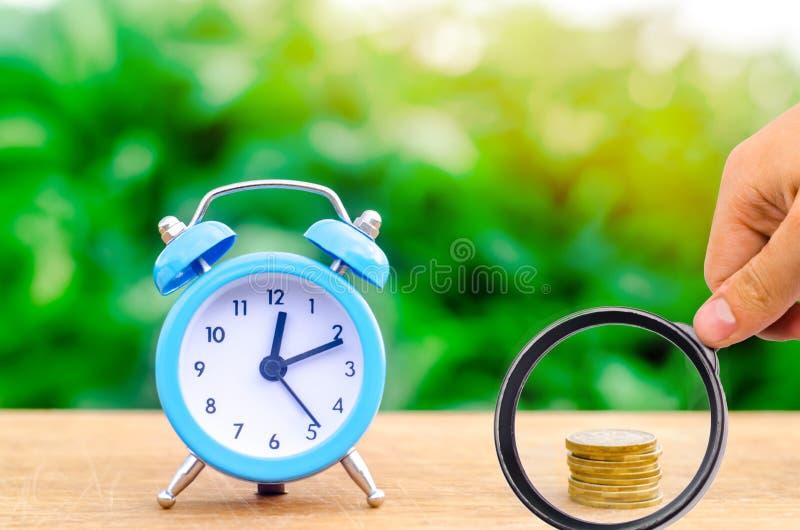 Wekker en geld op groene bokehachtergrond Het concept tijd is geld bedrijfs financi?le idee?n besparing financieel royalty-vrije stock afbeeldingen