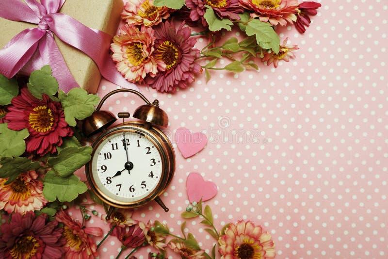 Wekker en giftvakje met rozenboeket met ruimteexemplaar op roze stipachtergrond stock foto's