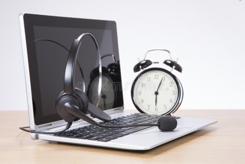 Wekker en hoofdtelefoon op laptop toetsenbord royalty-vrije stock fotografie