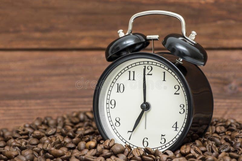 Wekker en koffiebonen op een houten achtergrond Wekker die zich op de bonen van koffie bevinden Het Concept van de koffietijd royalty-vrije stock afbeelding