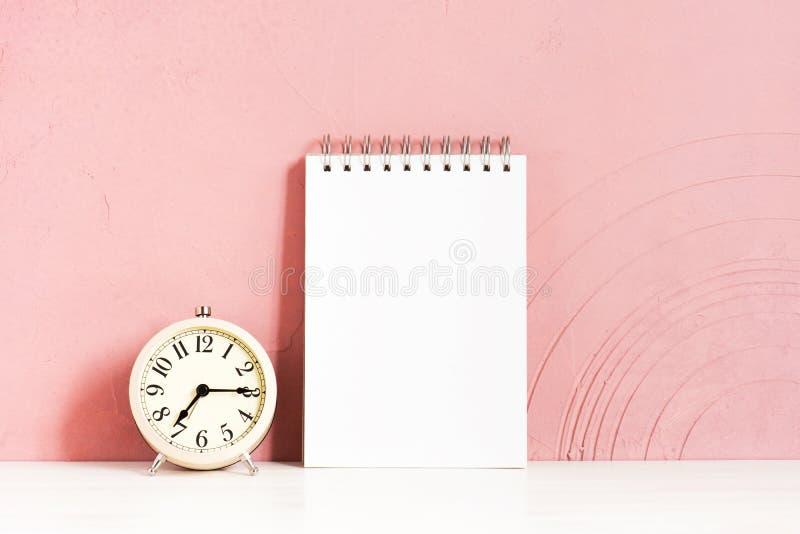 Wekker en lege blocnote op de houten witte lijst royalty-vrije stock foto's