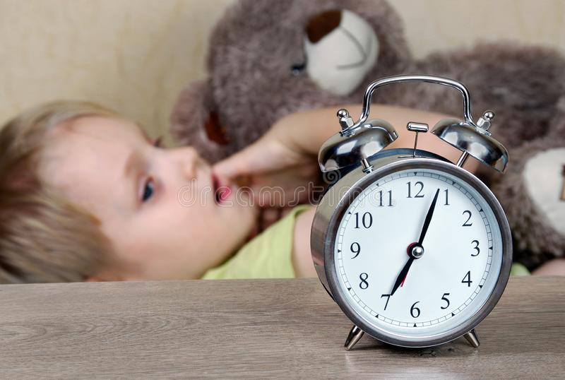 Wekker, het wekken wekker en gewekte baby zeven in de ochtend stock afbeeldingen