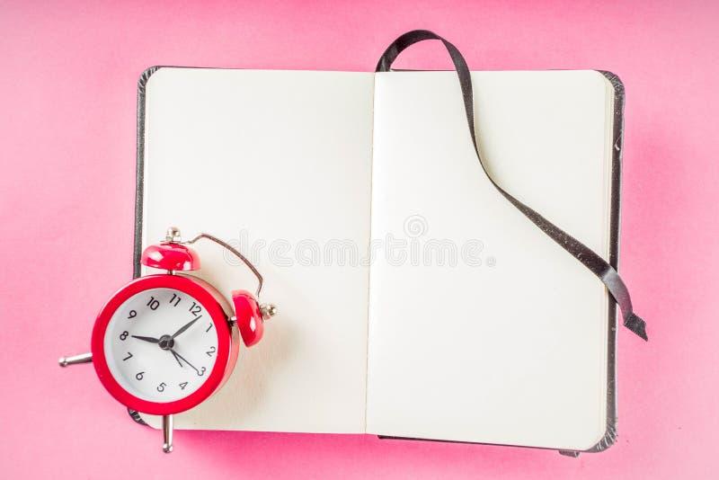 Wekker met blocnote op heldere roze lijst royalty-vrije stock foto's