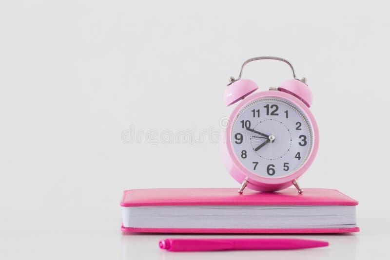 wekker met notitieboekje op witte achtergrond stock foto's