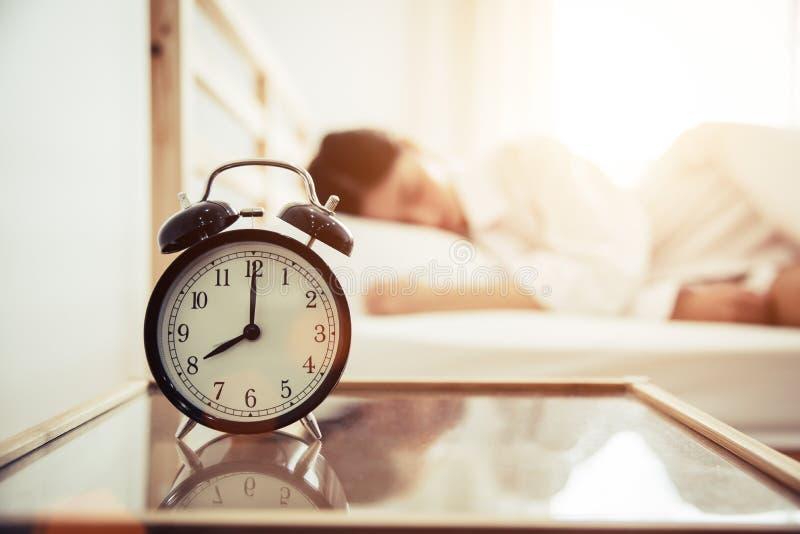Wekker met schoonheidsvrouw op achtergrond Ochtend en Lui tijdconcept Slaapkamerthema stock foto