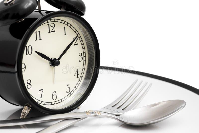 Wekker met vork en mes op de plaat op wit Tijd te eten Gezond voedselconcept royalty-vrije stock afbeelding
