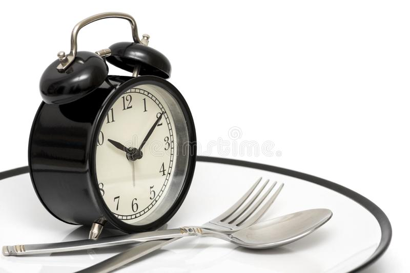Wekker met vork en mes op de plaat op wit Tijd te eten Gezond voedselconcept royalty-vrije stock fotografie