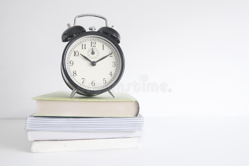 Wekker op een stapel van boeken op een houten plank Witte muurachtergrond en lege exemplaarruimte royalty-vrije stock afbeeldingen