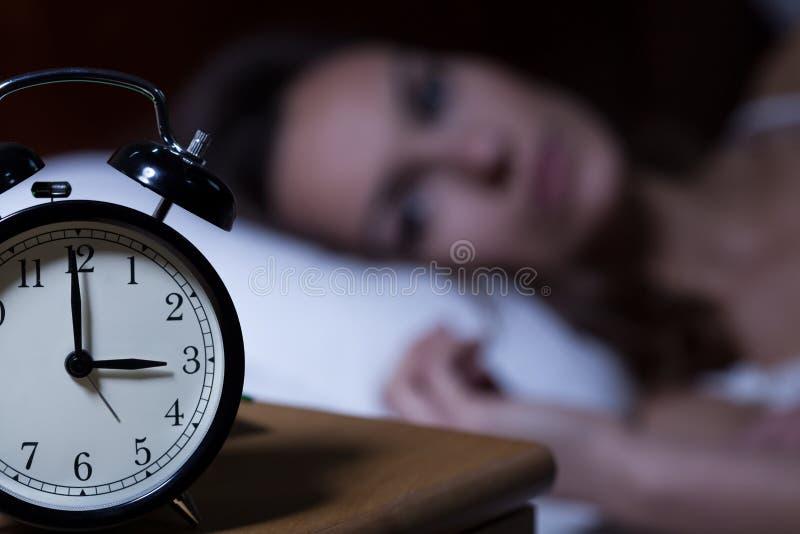 Wekker op nachtlijst stock afbeelding