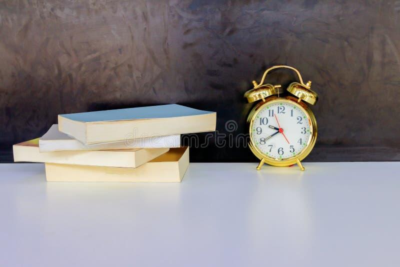Wekker oud uitstekend goud en boek over wit op zwarte achtergrond Met exemplaarruimte stock afbeelding