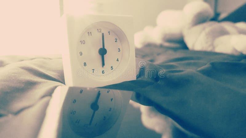Wekker 6 uur in de ochtend op het bed thuis Van de achtergrond ochtendtijd concept royalty-vrije stock afbeelding
