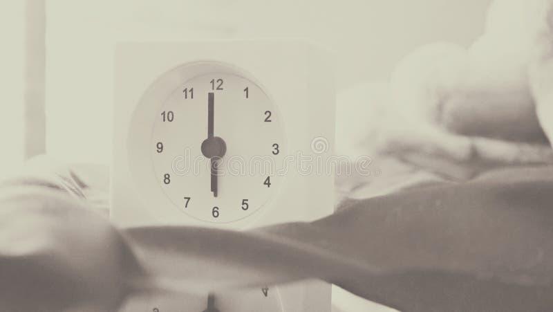 Wekker 6 uur in de ochtend op het bed thuis Van de achtergrond ochtendtijd concept royalty-vrije stock fotografie