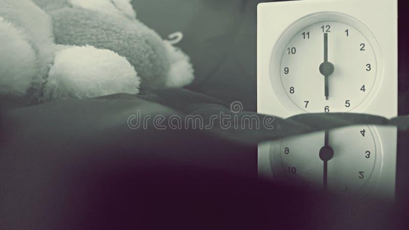 Wekker 6 uur in de ochtend op het bed thuis Van de achtergrond ochtendtijd concept stock foto