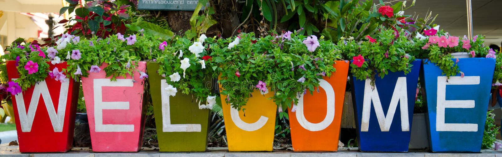 Welcome. Clay pots and planting flowers that welcome message stock photography
