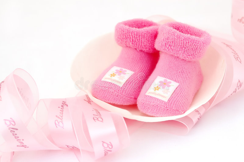 Welcome babygirl!. Baby pink socks on magnolia petal with pink ribbon