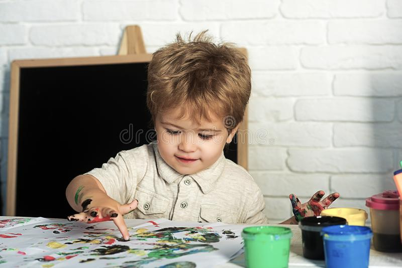 Welcome back to school. Drawing lessons. The boy draws with finger with paints. stock photos